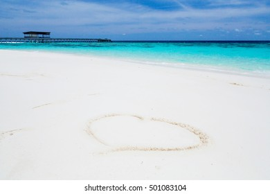 Heart drawn in the sand in the Maldives. Beach background. Top view