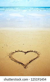 A heart drawn in the sand on the beach. Romantic design element.