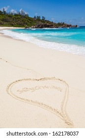 heart drawn in the sand and Seascape view with a huge stones, Seychelles, La Digue island