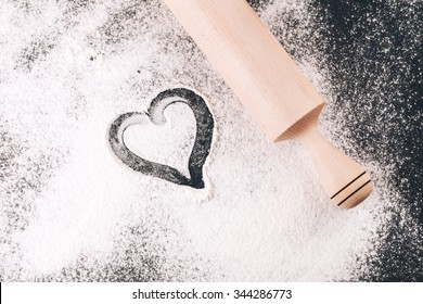 Heart drawn in scattered flour alongside a wooden rolling pin on  black background