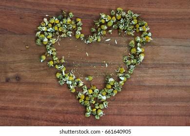 heart of dried chamomilla flower heads on wooden board