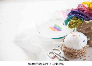 The heart is embroidered with a cross on the white canvas. Rainbow threads. White background. Needle and scissors.