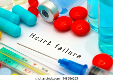 Heart failure - diagnosis written on a white piece of paper. Syringe and vaccine with drugs.