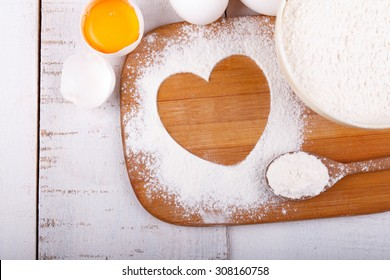 Heart of flour on wooden board on a kitchen table with a bowl of flour and eggs. Cooking