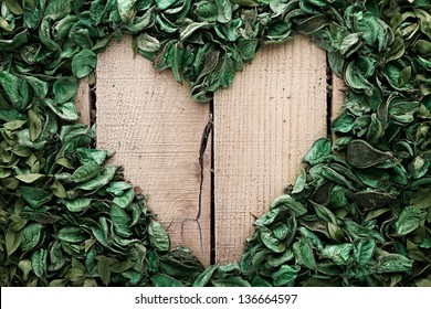 heart frame made of leaves on wooden background