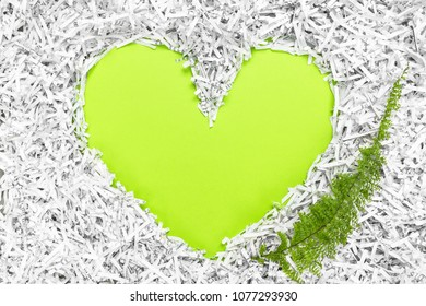 Heart frame made of shredded paper and a green leaf. Recycling and environment conservation concept.