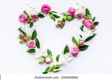 Heart frame roses and buds on a white background. Decorative floral element for design of greeting or postcards. Wedding flat lay