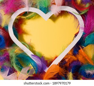 A heart frame with a yellow copy space in the middle with borders made of colorful feathers. Taken from the above. Diversity and inclusion concept