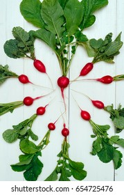 Heart of  fresh organic red radishes with tops on white wooden background, top view. Vegetable background