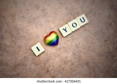 heart with gay rainbow flag and words i love you on a vintage  paper background. concept