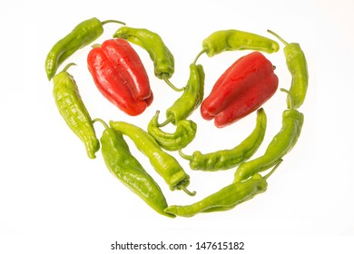 A heart of green and red peppers over white background