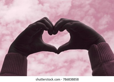 Heart hand of a girl or woman with sky and cloudy on Sakura tone style image