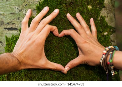Heart hand on tree with moss by man and woman, loving the nature