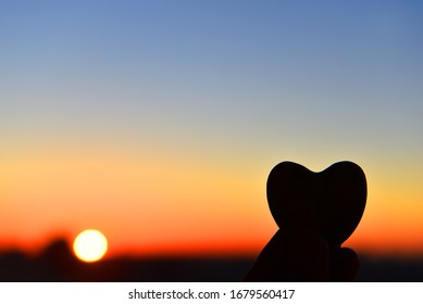heart in hands, against the backdrop of a beautiful sunset. hope.