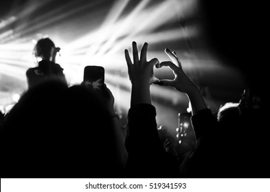 Heart of the hands, fingers. Heart hands. The gesture of love. Concert in the heart of the glare of floodlights. Black and white. Valentine's day