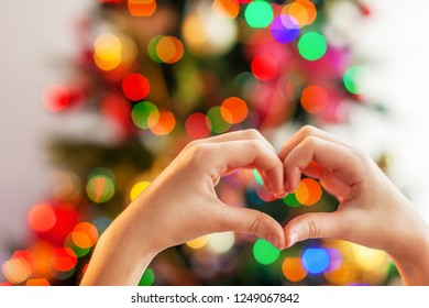 Heart from the hands in front of  christmas tree