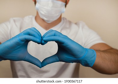 a heart from the hands on the background of a blurry masked man. the concept of love. people's health. blue-gloved hands.