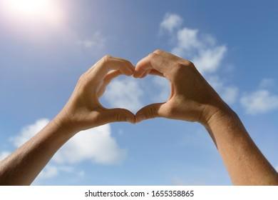 Herzhandsymbol vor dem blauen sonnigen Himmel