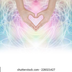 Heart Healing Energy -  Hands forming a heart shape on a swirling pastel rainbow energy background fading into white at the base