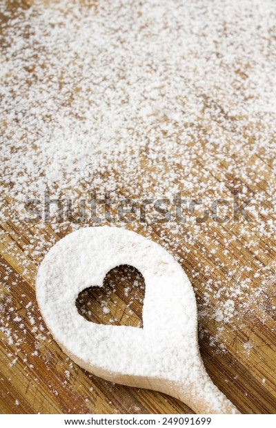 Heart hole spoon on the wooden pastry board - baking background