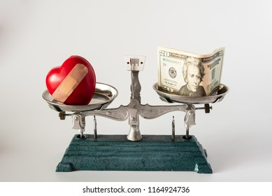 Heart injury model and dollar money on pan weight scale on white background.Health insurance concept.