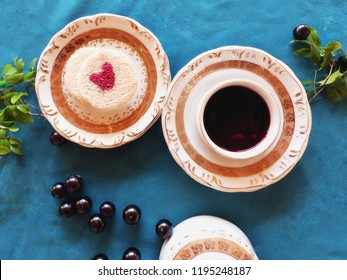 Heart of jabuticaba jelly in center of slice of bread cut in circle container of fine crockery with golden edges fruits and leaves on turquoise blue fabric towel