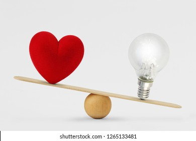 Heart and light bulb on scale - Concept of brain priority over heart in life