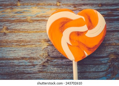 Heart lollipop candy on wood background - Vintage effect style pictures
