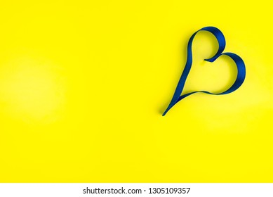 Heart made from blue satin ribbon on yellow background with copy space. Valentine's Day concept.