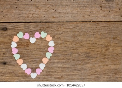 A heart made of candy conversation hearts on barn wood with nails