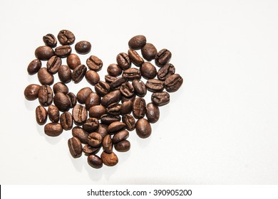 Heart made from coffee beans on white background with space for text