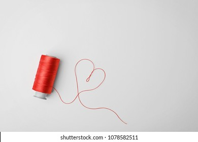 Heart made of color sewing thread and spool on white background, top view