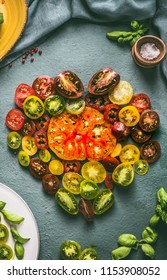 Heart made with colorful sliced tomatoes , top view