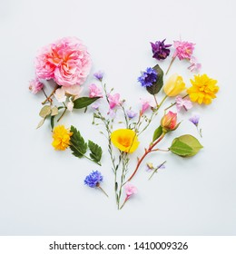 heart made of colorful spring flowers and leaves. Flat lay. Creative arrangement of flower petals and on white background. Blooming flowers concept. Minimal nature. Top view
