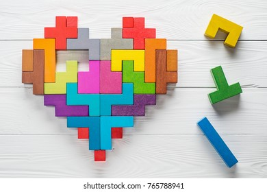 Heart made of colorful wooden shapes, top view, flat lay. Health background concept. Logical tasks. Conundrum, find the missing piece of the proposed.