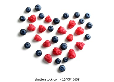 Heart made of delicious ripe berries on white background