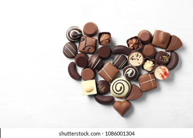 Heart made of different tasty chocolate candies on white wooden background