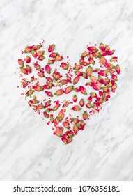 Heart made of dried rose flowers, on light gray marble background.
