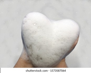 Heart made of foam on a white background. Big heart in the hands. Snow heart.