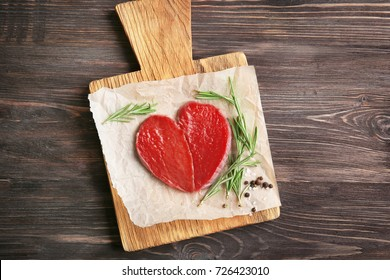 Heart made of fresh raw meat on wooden board