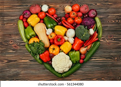 Heart made of fresh vegetables on wooden background