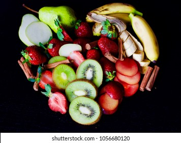 A heart made of fruits and cinnamon sticks with a black background