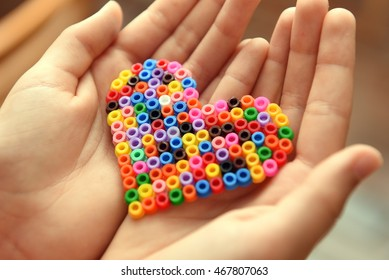 Heart made of hama beads in child's hands closeup.