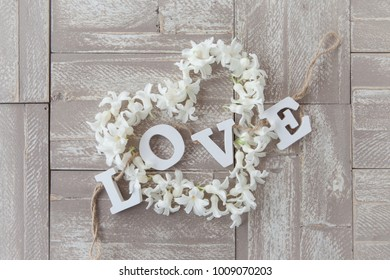 Heart made from hyacinths blossoms on rustic wooden background