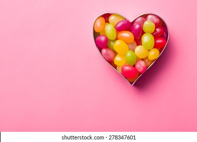 heart made from jelly beans on pink background