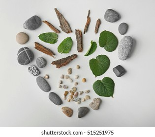 Heart made of leaves, pebbles and pieces of bark isolated on white