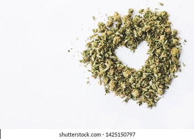 Heart made of marijuana shake isolated on white background