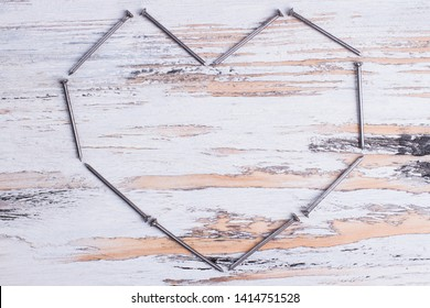 Heart made of nails on wooden background. Metal nails forming heart shape. Space for text.