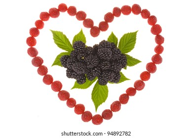 Heart made out of raspberries and blackberries. Top leaves of blackberry. On white background