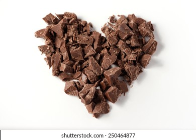 Heart made with pieces of chocolate on white background, valentine's day, selective focus